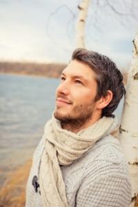 un homme heureux adossé contre un arbre regarde le ciel