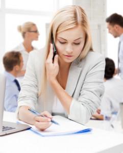 Une conseillere mutu-entreprise téléphone et ecrit sur une feuille